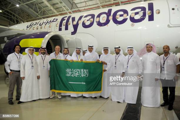 Saudi main staff employees display the national flag in front of a plane of the new Flydeal airlines company during the launching ceremony held at...