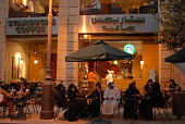 A Saudi male tourist wearing a traditional white dishdasha or thawb sits with a group of women wearing black abayas in a Starbucks coffeeshop in...