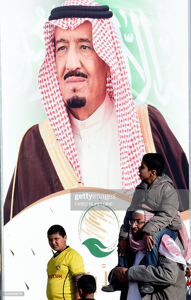 A Saudi man carries his child on his shoulders as they walk past a poster of King Salman bin Abdulaziz during the Janadriyah festival of Heritage and Culture held in the Saudi village of Al-Thamama, 50 kilometres north of the capital Riyadh, on February 8, 2016. / AFP / FAYEZ NURELDINE