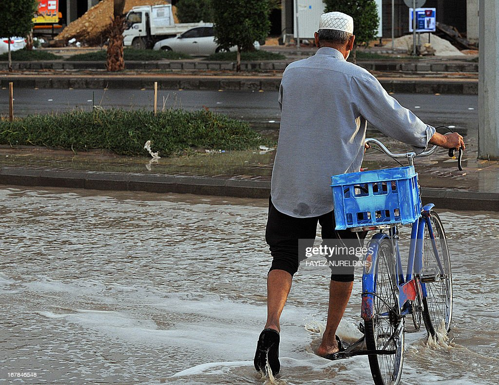 A Saudi man crosses a flooded street with his bike on May 1, 2013, in the north of the Saudi capital Riyadh. Sixteen people have died and three more are missing in Saudi Arabia after downpours caused flash floods in several areas of the desert kingdom, the civil defence authorities said. AFP PHOTO / FAYEZ NURELDINE