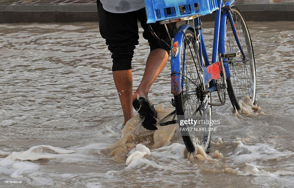 A Saudi man crosses a flooded street with his bike on May 1, 2013, in the north of the Saudi capital Riyadh. Sixteen people have died and three more are missing in Saudi Arabia after downpours caused flash floods in several areas of the desert kingdom, the civil defence authorities said.