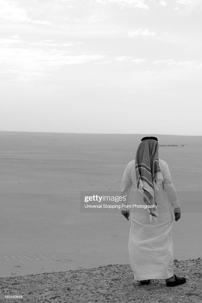 Saudi man looks out on desert : Stock Photo