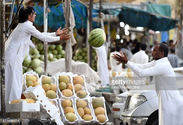 A Saudi man throws a watermelon at Otaiga public market in the Manfouha district of the capital Riyadh on June 17 2015 as the faithful prepare for...