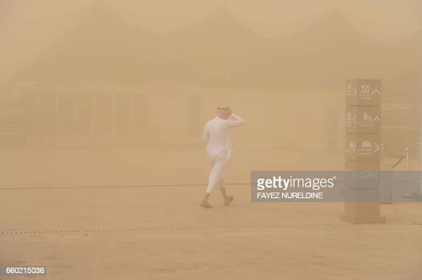 Saudi man walks in a sand storm during the annual King Abdulazziz Camel Festival in Rumah some 150 kilometres east of Riyadh on March 29 2017 The...
