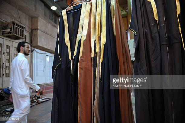 A Saudi man walks past a shop at the Mecca market in central Riyadh on August 26 days ahead of celebrations for Eid alFitr which marks the end of the...
