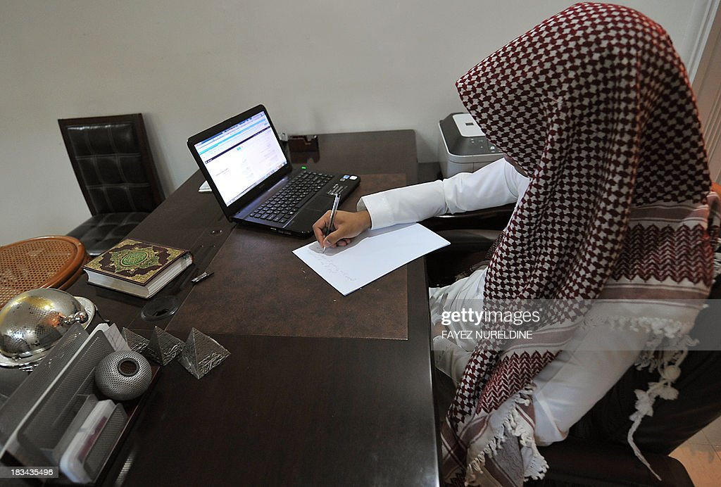 Saudi man writes notes in front of his laptop on his desk at his office in Riyadh, on October 6, 2013. Despite sitting on the world's largest wealth of oil, Saudis complain their salaries are not enough to make ends meet, and have taken to Twitter demanding better income.