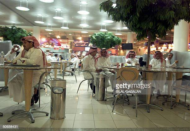 Saudi men gather a Starbucks Cafe in a shopping mall in Riyadh 07 June 2004 A threat bearing the hallmarks of the AlQaeda terror network and vowing...