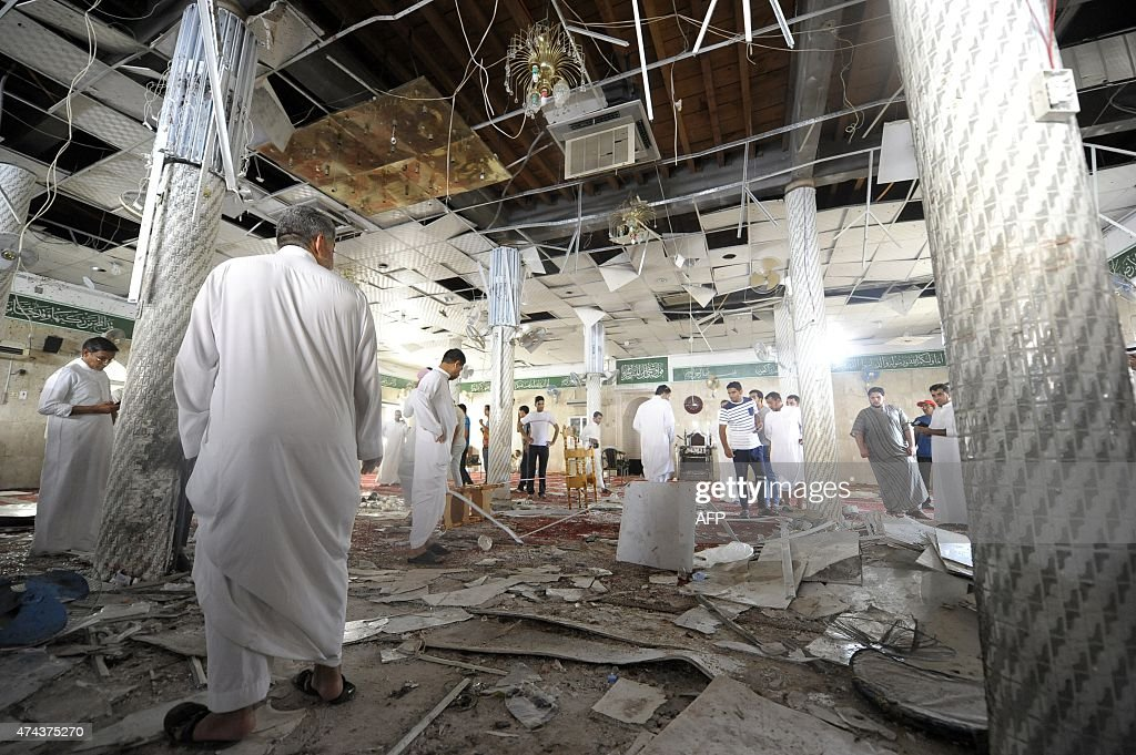 Saudi men gather around debris following a blast inside a mosque in the mainly Shiite Saudi Gulf coastal town of Qatif 400 kms east of Riyadh on May...