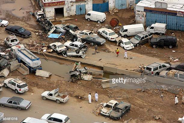 Saudi men inspect damages in the Red Sea city of Jeddah on November 29 2009 following a flash flood earlier this week A downpour on November 25...