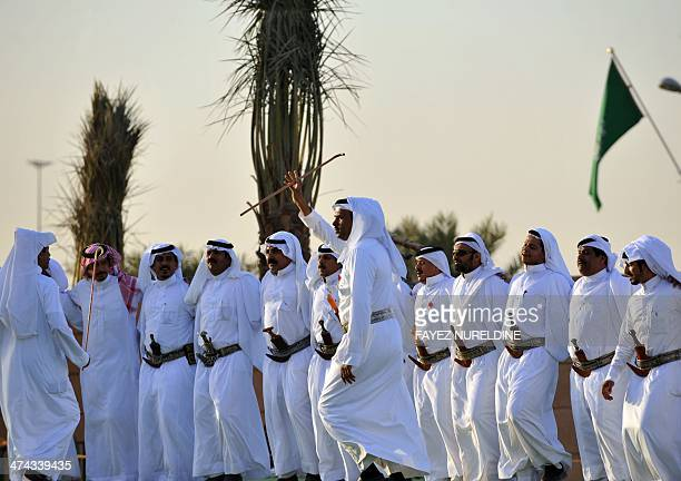Saudi men perform a traditional dance the Janadriyah festival of Heritage and Culture held in the Saudi village of AlThamama 50 kilometres north of...
