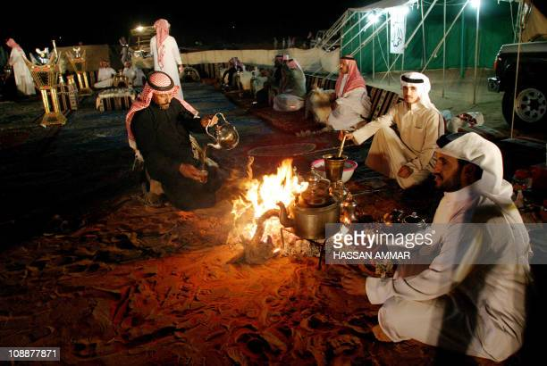 Saudi men sit by a bonfire outside a tent in the Hael desert around 700 kms north of downtown Riyadh 02 June 2007 Known for its old forts and...