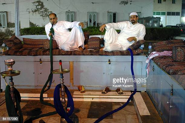 Saudi men spend an evening smoking waterpipes on outdoor wooden benches in the old town Jeddah Saudi Arabia 2nd December 2005