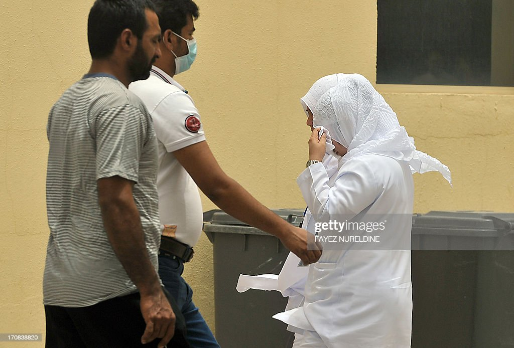 Saudi nurses and citizens walk outside the King Fahad hospital in the city of Hofuf, some 370 kilometres East of the capital Riyadh, on June 16, 2013. In the East of Saudi Arabia, where outbreaks of the MERS virus have been most concentrated, inhabitants have resumed their habits of shaking hands and kissing without worrying too much despite the death toll from the SARS-like virus reaching 32 in the kingdom.
