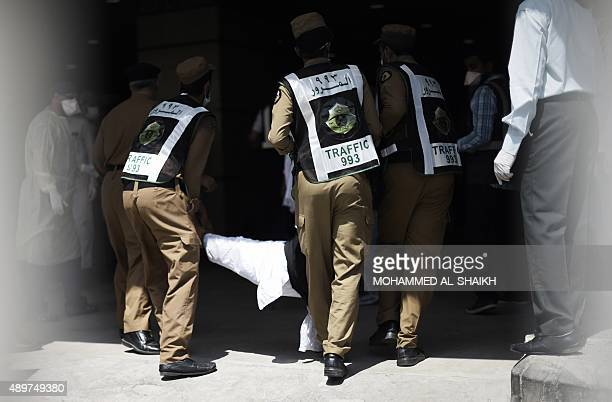 Saudi policemen carry an injured pilgrim outside an emergency hospital following a deadly stampede in Mina near the holy city of Mecca on the first...