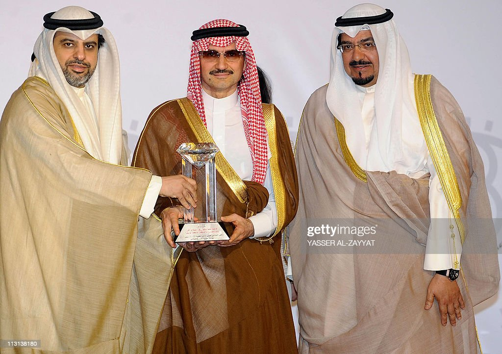 Saudi Prince Alwaleed bin Talal (C) receives an award from Madi Khamis (L), secretary general of the Arab Media Forum, and Kuwaiti Oil and Information Minister Sheikh Ahmed al-Abdullah al-Sabah, at the opening of the eighth Arab Media Forum in Kuwait City on April 24, 2011.