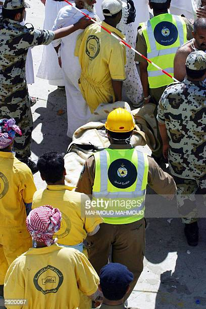 Saudi rescue workers evacuate a body following a stampede in the Mina valley near the Saudi holy city of Mecca 01 February 2004 A total of 244 people...