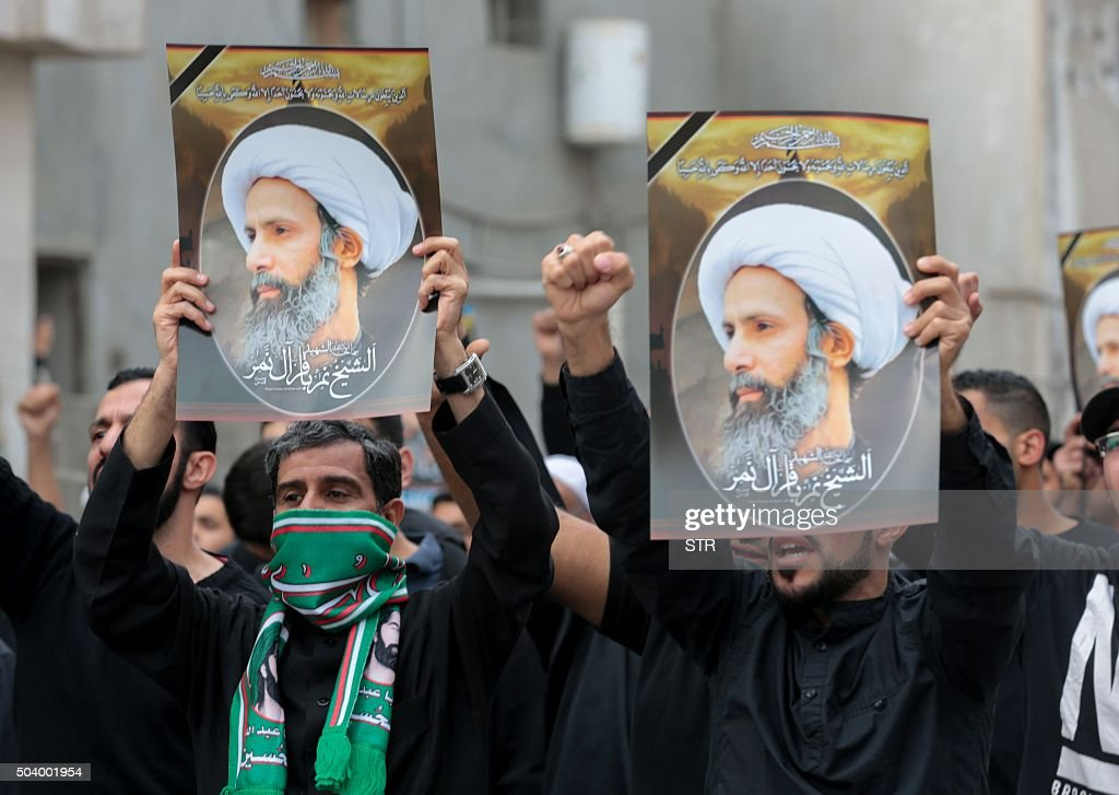 Saudi Shiite men hold placards bearing portraits of prominent Shiite Muslim cleric Nimr alNimr during a protest on January 8 2016 in the eastern...