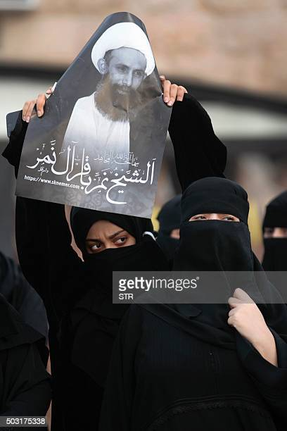 A Saudi Shiite woman holds a placard bearing a portrait of prominent Shiite Muslim cleric Nimr alNimr during a protest in the eastern coastal city of...