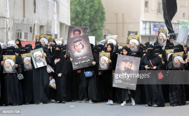 Saudi Shiite women hold placards bearing a portrait of prominent Shiite Muslim cleric Nimr alNimr during a protest on January 8 2016 in the eastern...