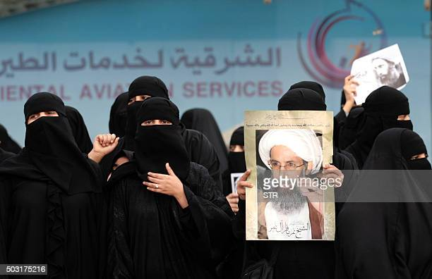 Saudi Shiite women hold placards bearing portraits of prominent Shiite Muslim cleric Nimr alNimr during a protest in the eastern coastal city of...