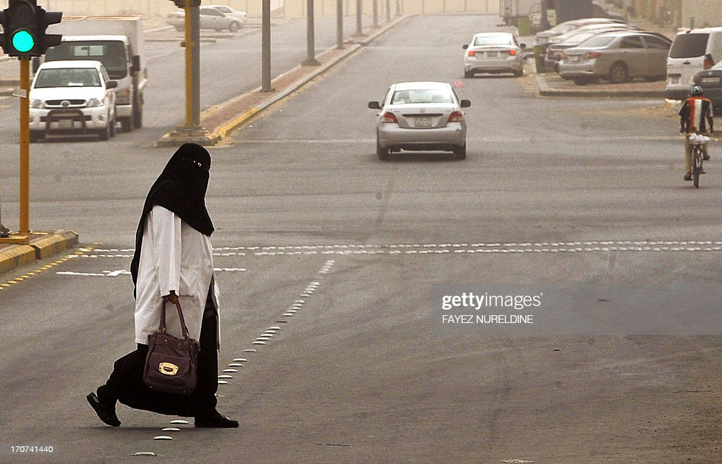 A Saudi staff nurse crosses the street on her way to the King Fahad hospital in the city of Hofuf, 370 kms East of the Saudi capital Riyadh, on June 16, 2013. Four people have died from the MERS virus in Saudi Arabia, bringing the death toll from the SARS-like virus in the kingdom to 32, the health ministry said. The World Health Organisation announced that the global death toll from MERS had reached 33, with 28 of them in the kingdom. The virus is a member of the coronavirus family, which includes the pathogen that causes Severe Acute Respiratory Syndrome (SARS).