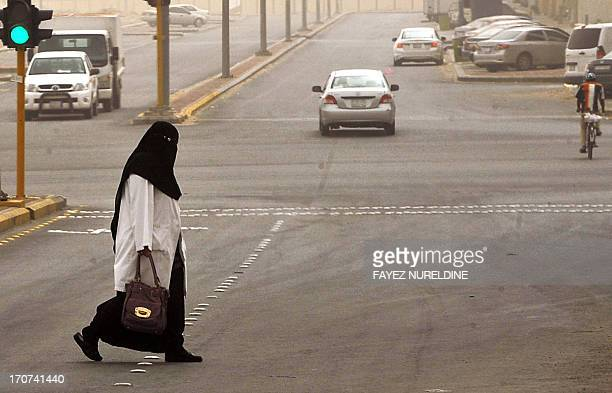 A Saudi staff nurse crosses the street on her way to the King Fahad hospital in the city of Hofuf 370 kms East of the Saudi capital Riyadh on June 16...
