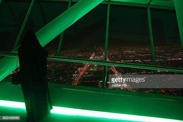 Saudi woman looks out over the skyline view of the city from the 99th floor the viewing floor at The Kingdom tower on December 7 2015 in Riyadh Saudi...