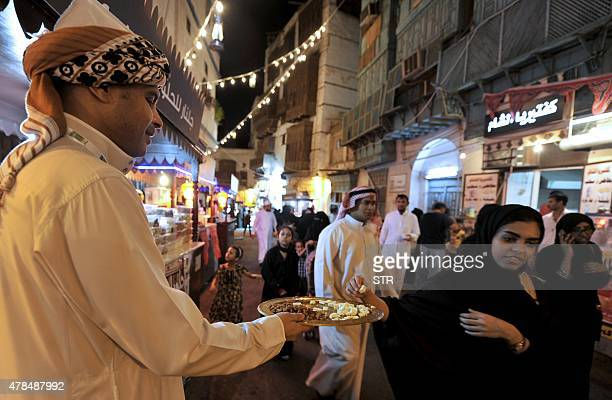 A Saudi woman rakes a traditional sweet on offer during a festival to celebrate the Muslim holy fasting month of Ramadan in the Saudi coastal city of...