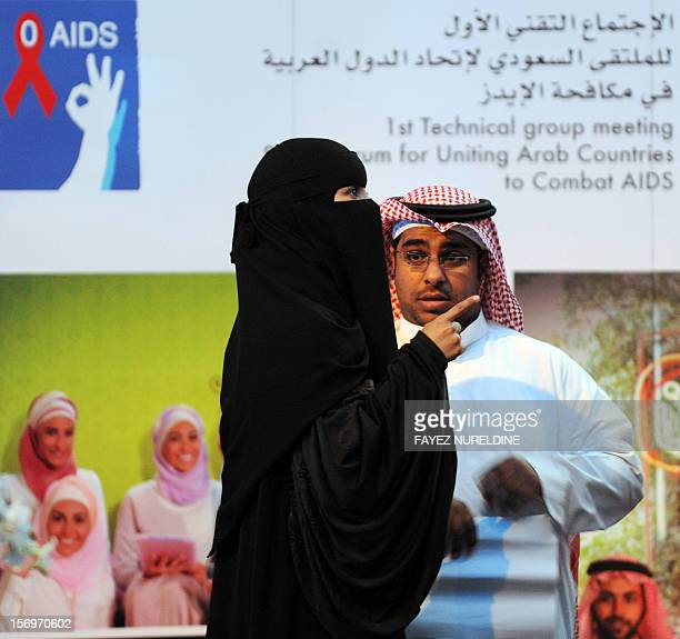 A Saudi woman talks to a man during the first Technical group meeting of the Saudi forum for Uniting Arab Countries to Combat AIDS at a hotel in...