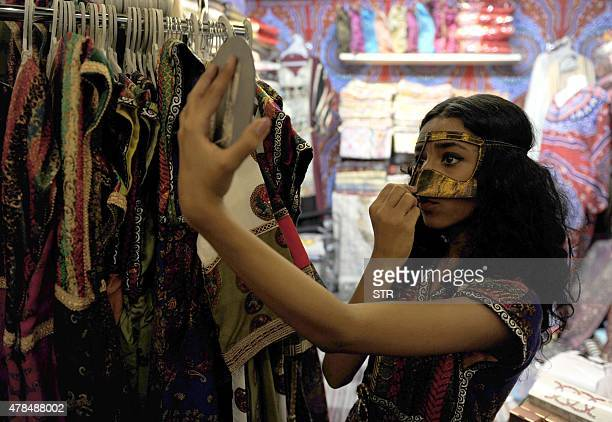 A Saudi woman tries on a mask at a shop during a festival to celebrate the Muslim holy fasting month of Ramadan in the Saudi coastal city of Jeddah...