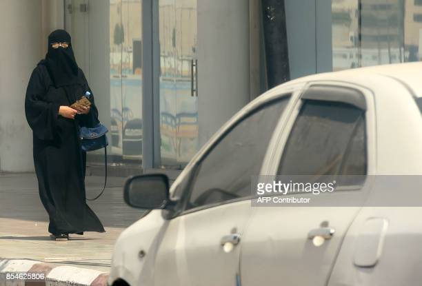 A Saudi woman walks near car down a street in the Saudi capital Riyadh on September 27 2017 Saudi Arabia will allow women to drive from next June...