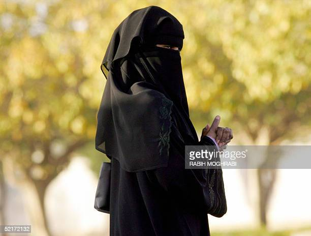 Saudi woman walks outside a polling station in Riyadh during the desert kingdom's first municipal elections 10 February 2005 Saudi men went to the...