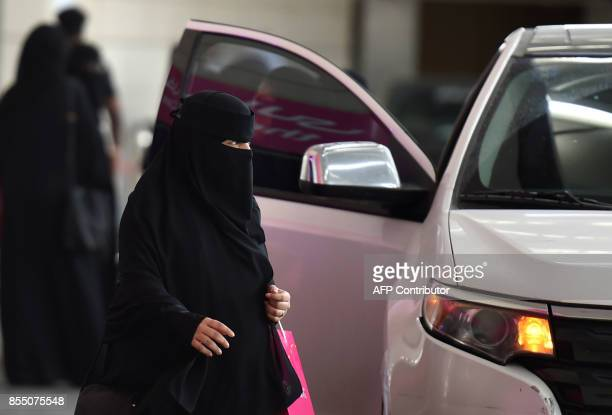 A Saudi woman walks past a car outside a hotel in the Saudi capital Riyadh on September 28 2017 Saudi Arabia will allow women to drive from June 2018...