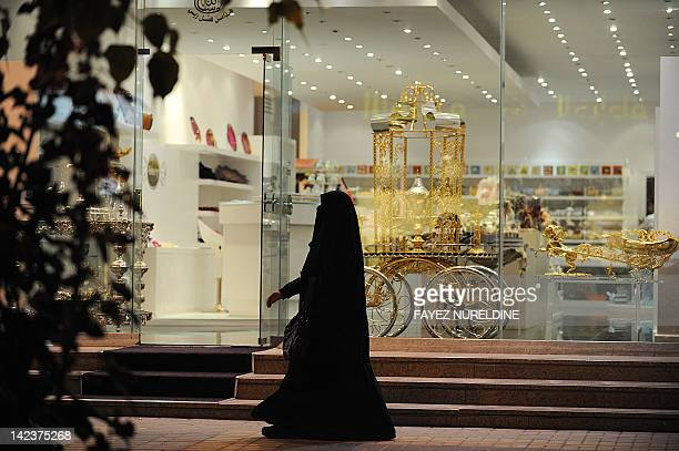 A Saudi woman walks past a chocolate store on February 14 2012 in the desert kingdom's capital Riyadh where open celebration of Valentine's Day is...