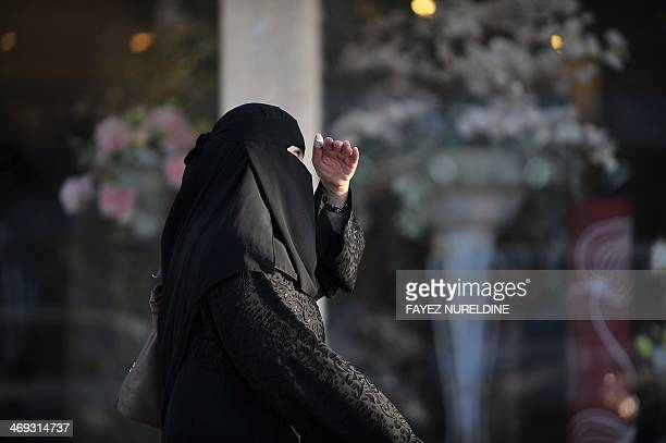 Saudi woman walks past a flower shop on the eve of Valentine's day in Riyadh on February 13 2014 Red roses lurk hidden in flower shop back rooms and...