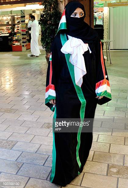 A Saudi woman wearing a 'Wold Cup' abaya or dress designed by local fashion designer Rania Khogeer with the colours of the Italian flag walks through...