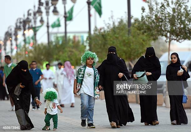 Saudi women and children walk on a street as they make their way to attend the celebrations marking the 84th Saudi Arabian National Day in the desert...