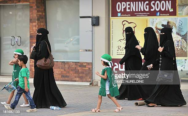 Saudi women and their children walk along a street as they make their way to a celebration rally marking the 83rd Saudi Arabian National Day in the...