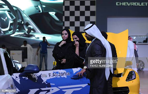 Saudi women look at a luxury chevrolet sport car during the 30th International Riyadh Motor Show on November 29 2016 in Riyadh In a Saudi economy...