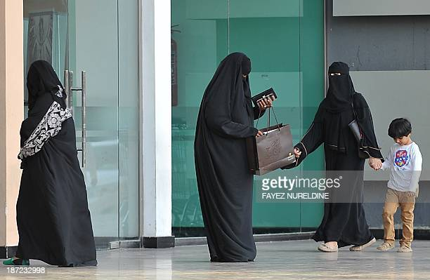 Saudi women stand at the entrance of a shoopping mall on November 7 2013 Saudi Arabia has the Arab world's largest economy but the unemployment rate...