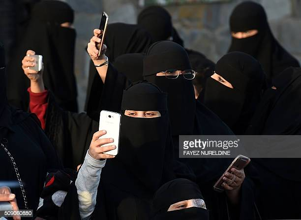 Saudi women use their mobile phones during the Janadriyah festival of Heritage and Culture held in the Saudi village of AlThamama 50 kilometres north...