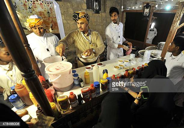 Saudi women wait to be served at a food stall during a festival to celebrate the Muslim holy fasting month of Ramadan in the Saudi coastal city of...