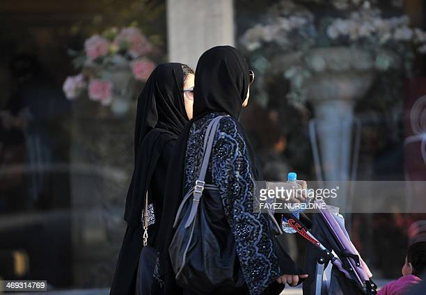 Saudi women walk past a flower shop on the eve of Valentine's day in Riyadh on February 13 2014 Red roses lurk hidden in flower shop back rooms and...