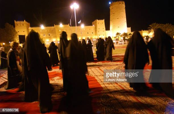 Saudi women walk towards a replica of Masmak castle in Al Aldria outside Riyadh during a celebration for the Human rights conference in Saudi October...
