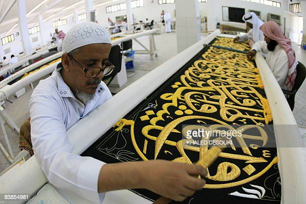 Saudi workers sew Islamic calligraphy in gold thread on a drape to cover the Kaaba at the Kiswa factory in the holy city of Mecca on November 29 2008...