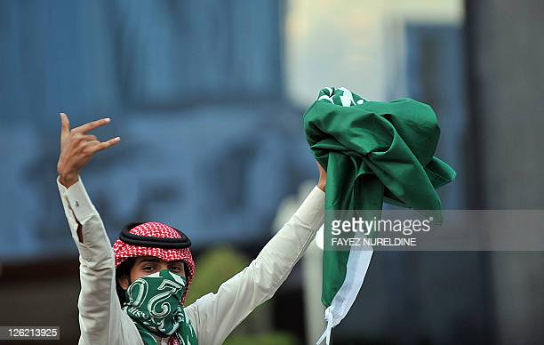 A Saudi youth holds up a folded national flag during celebrations of the 81st Saudi Arabian National Day in the desert kingdom's capital Riyadh on...