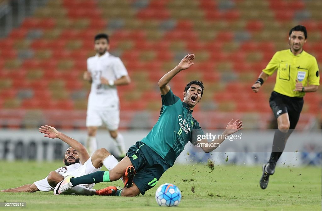 Saudi's Al-Ahli player Hussain al-Mogahwi (C) falls to the ground after being tackled during their AFC Champions League group D football match against Qatar's El-Jaish club at the King Abdullah Spots City in Jeddah on May 3, 2016. / AFP / STRINGER