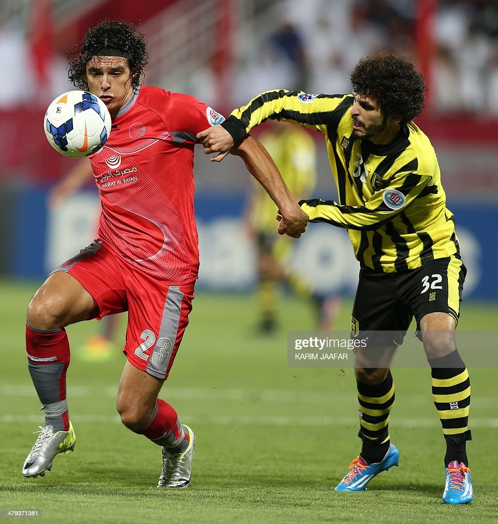 Saudi's AlIttihad club player Mohammed Ali challenges Qatar's Lekwiya player Sebastian Soria for the ball during their AFC Champions League group C...