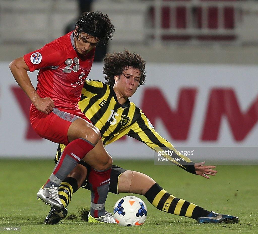 Saudi's AlIttihad player Jamal Abdulla challenges Qatar's Lekwiya player Sebastian Soria for the ball during their AFC Champions League group C...