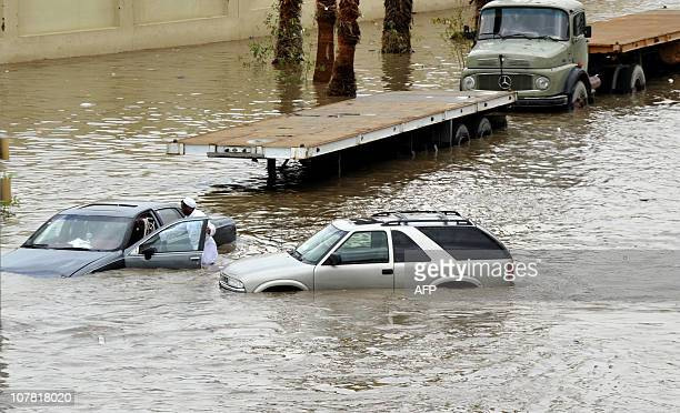 Saudis leave their vehicles in a flooded street following heavy rain in the Red Sea port city of Jeddah on December 30 2010 AFP PHOTO/AMER HILABI
